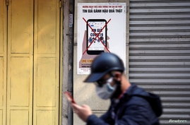 FILE - A man uses a smartphone as he walks past a poster warning against the spread of 'fake news' on the coronavirus, in Hanoi, Vietnam April 14, 2020.