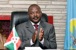 FILE - Burundi President Pierre Nkurunziza claps after signing the new constitution at the Presidential Palace in Gitega Province, June 7, 2018.