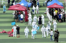 Medical workers in protective suits help people lining up inside a sports center for nucleic acid tests, following new cases of coronavirus disease (COVID-19) in Beijing, China, June 15, 2020.