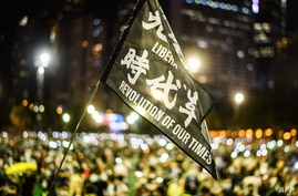Attendees raise a flag that reads 'Liberate Hong Kong Revolution Of Our Times' during a candlelit remembrance in Victoria Park…
