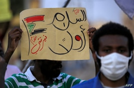 """A demonstrator holds up a sign reading in Arabic """"peace first, Nertiti sit-in"""" along with a drawn Sudanese flag, during a…"""