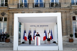 French President Emmanuel Macron (C) speaks flanked by French Defence Minister Florence Parly (L) and French Junior Minister of…