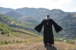 Priest Ter Abel prays for peace outside the village of Movses on the Armenian-Azerbaijani border on July 15, 2020. - Defence…