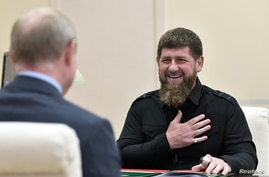Head of the Chechen Republic Ramzan Kadyrov speaks during a meeting with Russia's President Vladimir Putin at a residence near…