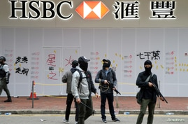 Armed undercover police officers guard a vandalized HSBC bank branch in Wan Chai during demonstrations on the New Year's Day in…