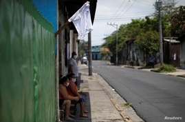 Ana Orellana, a street vendor of coffee, sits outside a house and near a white flag as a sign to ask for food, in a low-income…