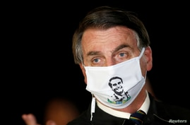 Brazil's President Jair Bolsonaro speaks with journalists while wearing a protective face mask as he arrives at Alvorada Palace…