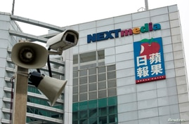 FILE - A security camera is seen in front of the headquarters of Apple Daily and Next Media in Hong Kong.