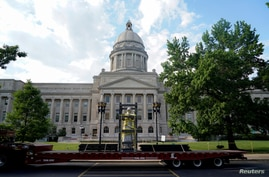 A caged statue of Confederate President Jefferson Davis departs on a truck after being removed from Kentucky state capitol