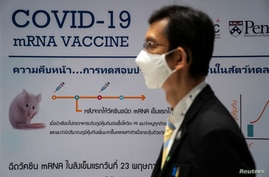 A man wearing a face mask stands next to a board showing the progress of developing an mRNA type vaccine candidate for the…