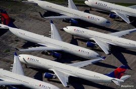 FILE PHOTO: Delta Air Lines passenger planes are seen parked due to flight reductions made to slow the spread of coronavirus…