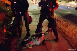 Journalist Justin Yau lies handcuffed on the ground with police officers standing beside him, after they dispersed protesters during a demonstration against racial injustices in Portland, July 1, 2020 in this still image obtained from social media video.