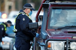 Police stop drivers at a checkpoint, set up in response to the state of Victoria's surge in coronavirus disease (COVID-19)…