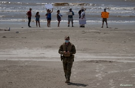 A police officer walks away from local residents protesting closed beaches on the 4th of July amid the global outbreak of the…