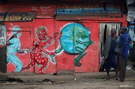 Vendors carrying traditional medicine in jerrycans, stand outside a stall which has graffiti against the spread of the…