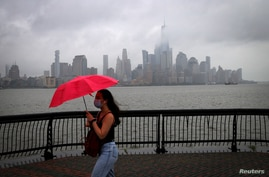 A woman shields herself from rain and wind with an umbrella as she walks along the Hudson River in front of the skyline of New…