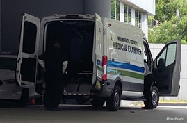 A body is loaded into a Miami-Dade County Medical Examiner's van outside Jackson Health Center, where coronavirus disease …