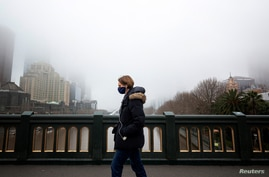 A person in a protective face mask walks along the Princes Bridge amidst a lockdown in response to an outbreak of the…