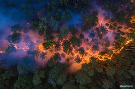 An aerial view shows a forest fire in Krasnoyarsk Region, Russia July 17, 2020. Picture taken July 17, 2020. Julia Petrenko…