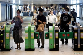 Passengers wearing protective face masks pass through the automated entranceway at a station amid the coronavirus disease …