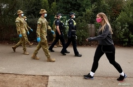 ADF personnel and Victorian police officers patrol a walking track as Melbourne remains in lockdown restrictions due to…