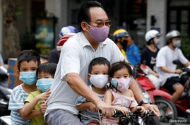 A man and his children, all wearing protective masks, ride a bicycle on a street during the coronavirus disease (COVID-19)…