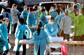 Medical personnel prepare to test hundreds of people lined up in vehicles June 27, 2020, in Phoenix, Arizona.