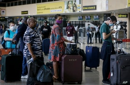 FILE - U.S. citizens queue to check in and be repatriated aboard an evacuation flight in Lagos, Nigeria.