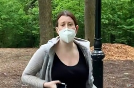 FILE - This image made from May 25, 2020 video provided by Christian Cooper, shows Amy Cooper with her dog talking to Christian Cooper in Central Park in New York.