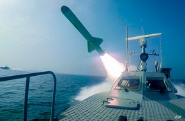 In this photo released Tuesday, July 28, 2020, by Sepahnews, a Revolutionary Guard's speed boat fires a missile .