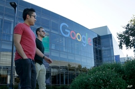FILE - Two men walk past a building on the Google campus in Mountain View, California.