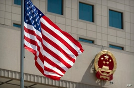 The American flag flies near the national emblem of China outside of the Bayi Building before a welcome ceremony for U.S…