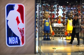 A man walks past statues of NBA players Stephen Curry of the Golden State Warriors, left, and Lebron James of the Los Angeles…