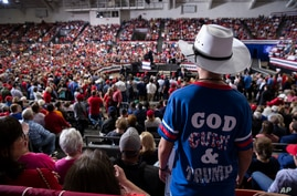 Supporters of President Donald Trump listen as he speaks during a campaign rally at the Monroe Civic Center in Louisiana.