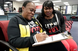 FILE - In this Jan. 8, 2019, file photo, former felon Yolanda Wilcox, left, fills out a voter registration form as her best…