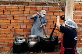 FILE - Walter Ferreira, left, and Laura Dure cook stew at a soup kitchen that feeds about 300 people daily in Luque, Paraguay, May 11, 2020.