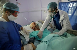 Medical workers attend to a COVID-19 patient in an intensive care unit at a hospital in Sanaa, Yemen, June 14, 2020.