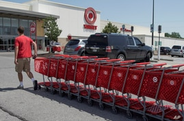 A Target employee returns shopping carts from the parking lot, in Omaha, Neb., Tuesday, June 16, 2020. American shoppers ramped…