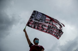 "Protester waves U.S. flag with ""Black Lives Matter"" spray painted on it, Washington, DC, June 19, 2020."