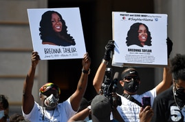 Signs are held up showing Breonna Taylor during a rally in her honor on the steps of the Kentucky State Capitol in Frankfort,…