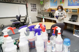 Charo Woodcock cleans a classroom at McClelland Elementary School, Monday, June 22, 2020, in Indianapolis. As the coronavirus…