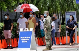 People wait in line at a walk-up testing site for COVID-19 during the new coronavirus pandemic, in Miami.