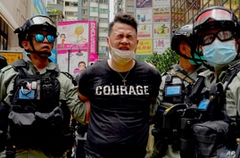 Police detain a protester after bering sprayed with pepper spray during a protest in Causeway Bay before the annual handover…