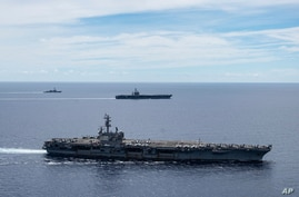 In this photo provided by U.S. Navy, the USS Ronald Reagan (CVN 76, front) and USS Nimitz (CVN 68, rear) Carrier Strike Groups.