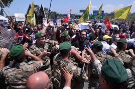 Hezbollah supporters scuffle with Lebanese army soldiers while protesting the visit by Gen. Frank McKenzie, the head of U.S. Central Command, outside ​​the Rafik Hariri International Airport in Beirut, Lebanon, July 8, 2020.