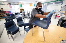 Des Moines Public Schools custodian Tracy Harris cleans chairs in a classroom at Brubaker Elementary School, Wednesday, July 8,…