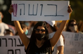"""An Israeli social worker holds a sign in Hebrew that reads, """"shame,"""" during a protest against the economic situation in the central Israeli town of Kfar Ahim, July 9, 2020."""