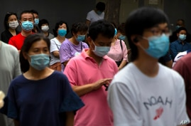 Parents and relatives wearing face masks to protect against the coronavirus wait for students to finish taking the final day of…