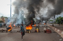 Anti-government protesters burn tires and barricade roads in the capital Bamako, Mali, Friday, July 10, 2020. Thousands marched…