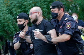 Police officers detain Alexander Chernykh, Kommersant newspaper journalist, during a rally to support Ivan Safronov near the…